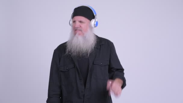 Mature bearded hipster man dancing while listening to music