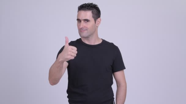 Happy handsome man giving thumbs up against white background
