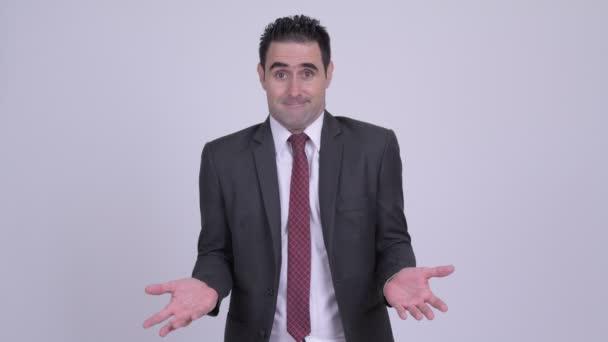 Handsome businessman shrugging shoulders against white background