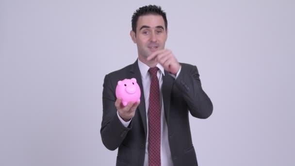 Šťastný podnikatel drží prasátko a cosi vysvětloval