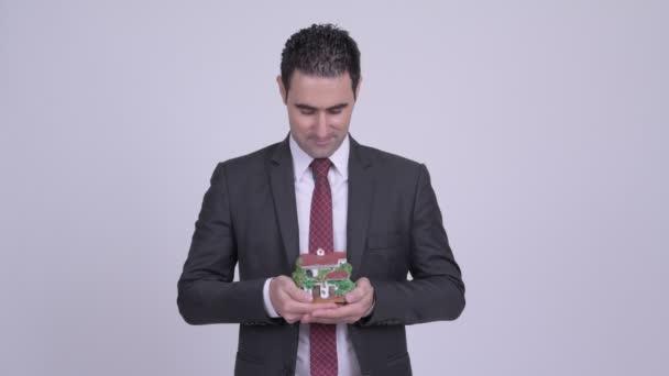 Happy pohledný podnikatel drží dům figurka