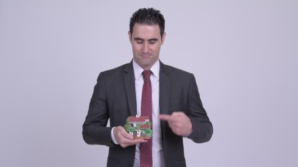 Šťastný podnikatel drží dům figurku a dává palec nahoru