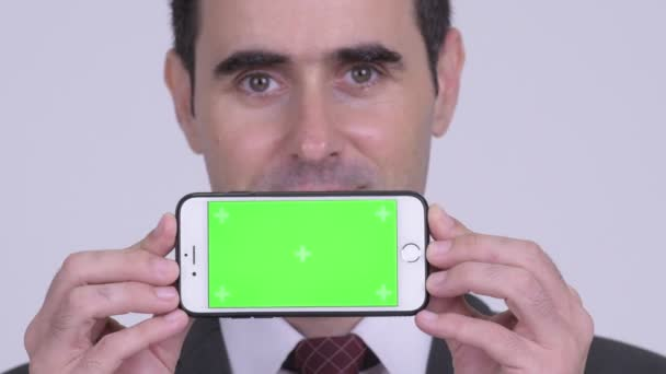 Closeup of happy handsome businessman showing phone