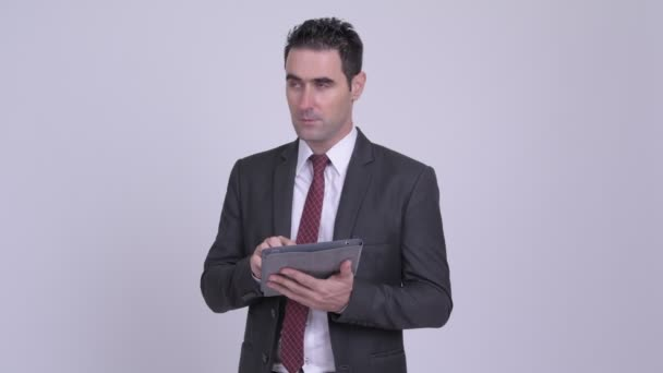 Happy handsome businessman thinking while using digital tablet