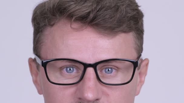 Eyes of hipster man wearing eyeglasses against white background