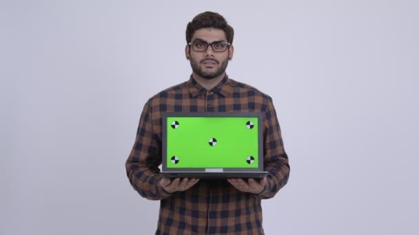 glücklich junge indische Hipster-Mann zeigt Laptop und sieht überrascht
