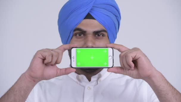 Face of happy young bearded Indian Sikh man showing phone