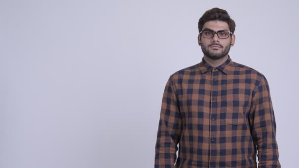 Studio shot of young bearded Indian hipster man against white background