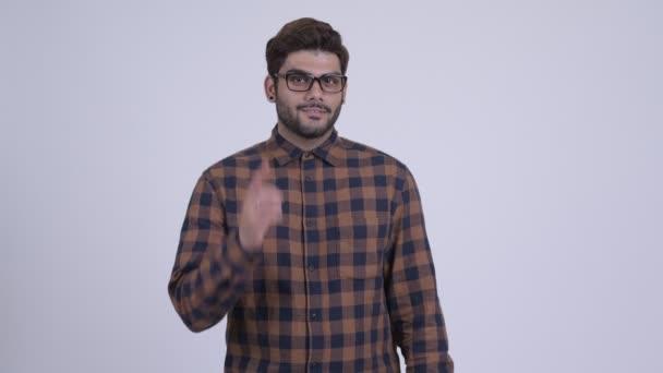 Boldog, fiatal szakállas indiai csípő ember felfelé mutató