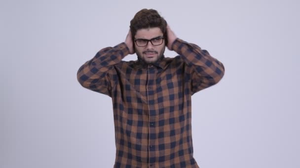 Stressed young bearded Indian hipster man not wanting to hear something