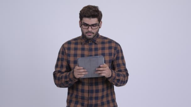Happy young bearded Indian hipster man thinking while using digital tablet