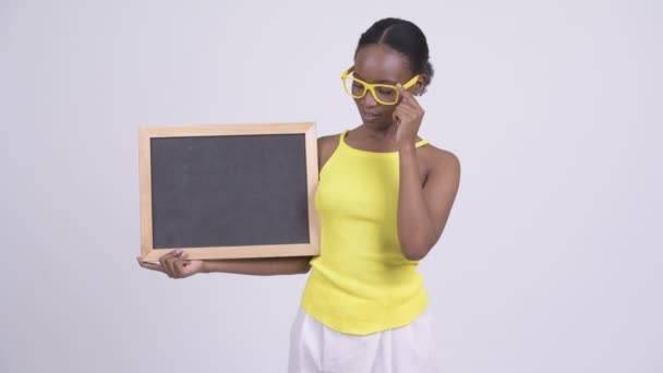 Young beautiful African Zulu woman wearing yellow sleeveless top against white background