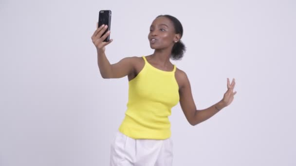 Young happy African woman video calling with phone