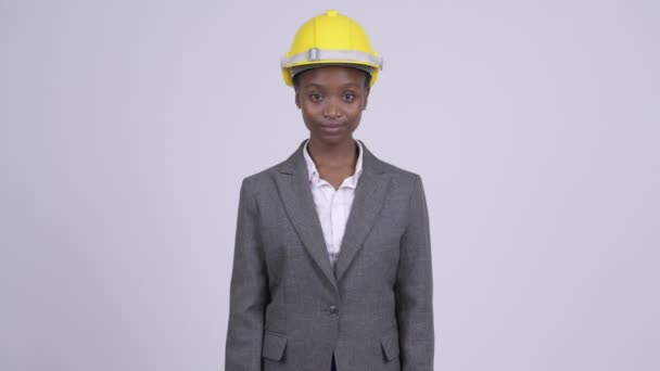Young beautiful African businesswoman wearing hardhat with arms crossed