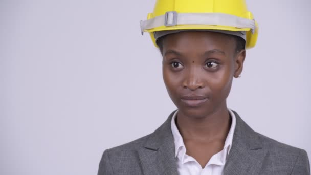 Face of young beautiful African businesswoman with hardhat thinking