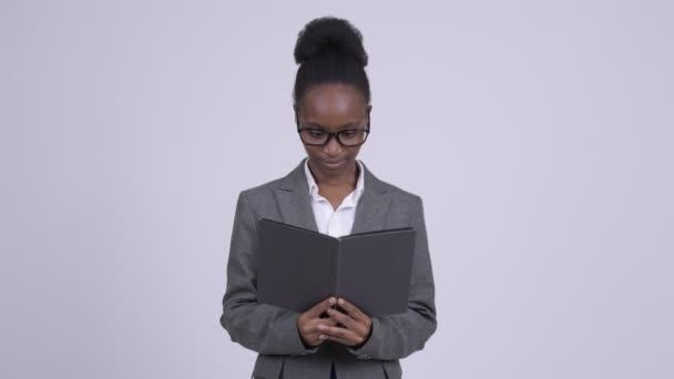 Mladá stydlivá africké podnikatelka čtení knihy a pokrývající obličej