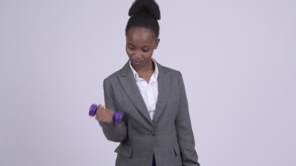 Young happy African businesswoman exercising with dumbbells