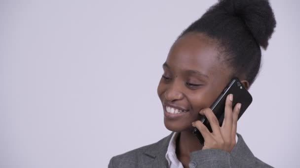 Young happy African businesswoman thinking while talking on the phone