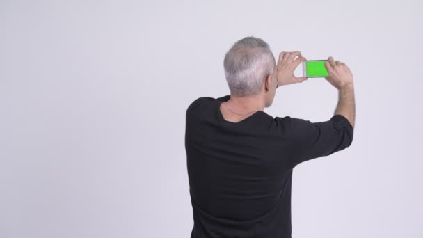 Rückansicht eines persischen Mannes beim Fotografieren mit dem Handy