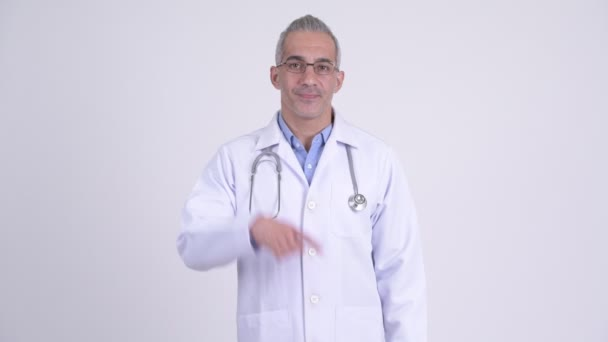 Happy Persian man doctor pointing up against white background