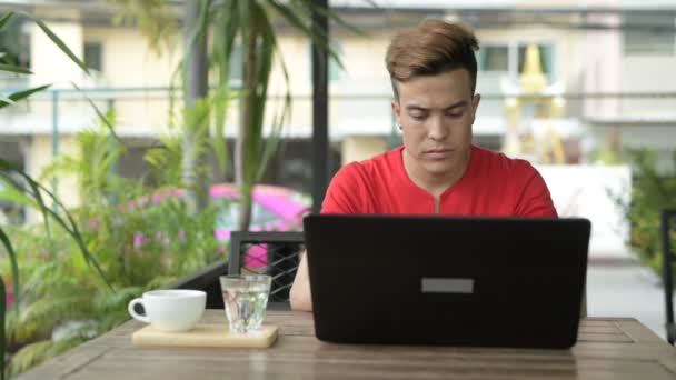 Happy young Asian man using laptop at the coffee shop outdoors