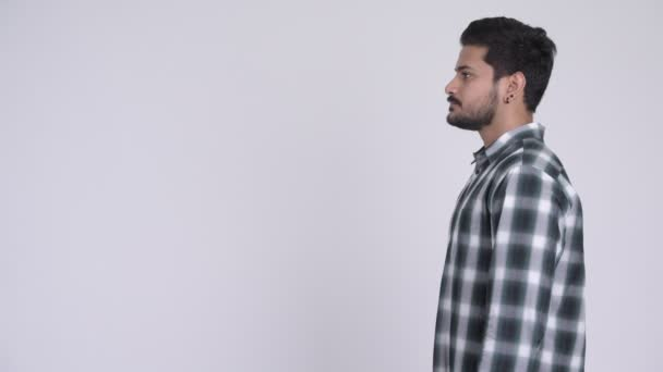 Profile view of young handsome bearded Indian man