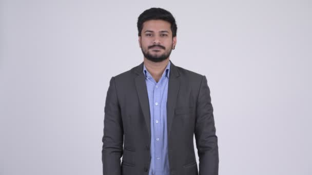 Portrait of young handsome bearded Indian businessman wearing suit