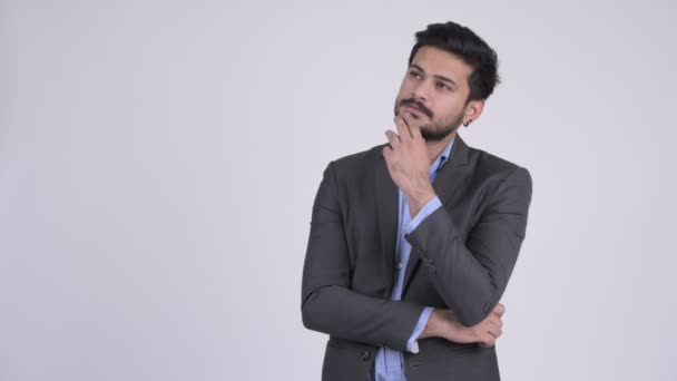 Young happy bearded Indian businessman thinking