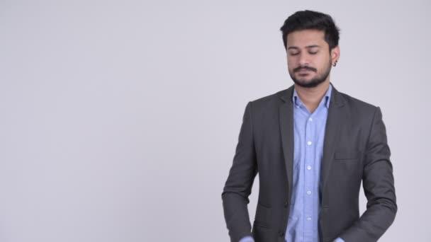 Boldog fiatal szakállas mutatja valami indiai üzletember
