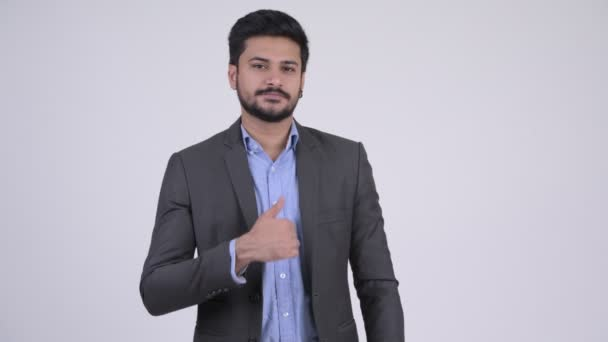 Young happy bearded Indian businessman giving thumbs up