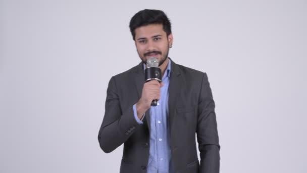 Mladý indický podnikatel jako moderátor s mikrofonem