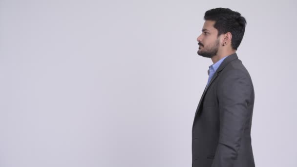 Profile view of young handsome bearded Indian businessman wearing suit