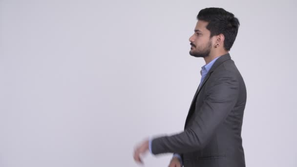 Profile view of young handsome bearded Indian businessman thinking