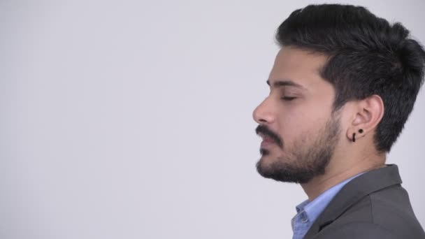 Profile view of young happy bearded Indian businessman talking