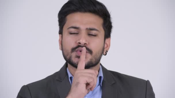 Mladý pohledný vousatý indický podnikatel s prstem na rtech