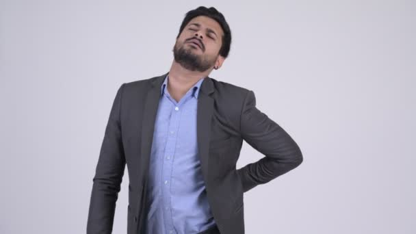 Young stressed bearded Indian businessman having back pain