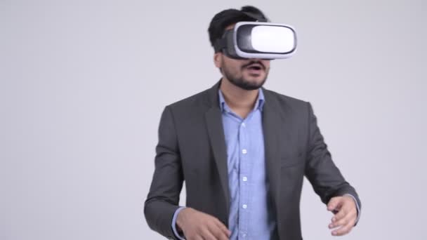 Young bearded Indian businessman using virtual reality headset