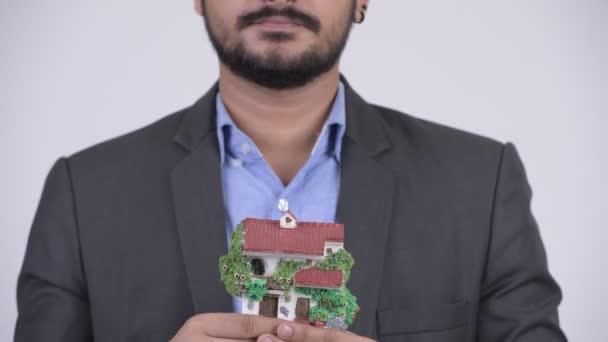 Mladý šťastný vousatý indický podnikatel drží dům figurka