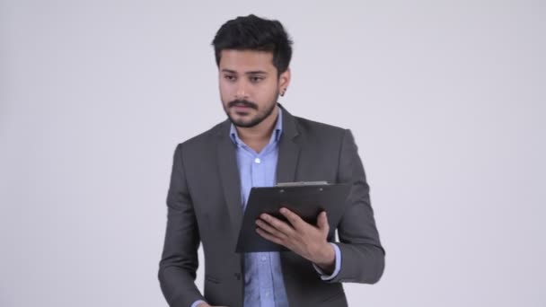 Young bearded Indian businessman directing while holding clipboard