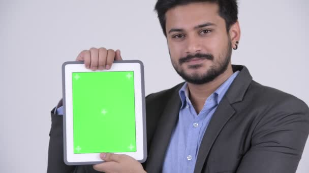 Young happy bearded Indian businessman showing digital tablet