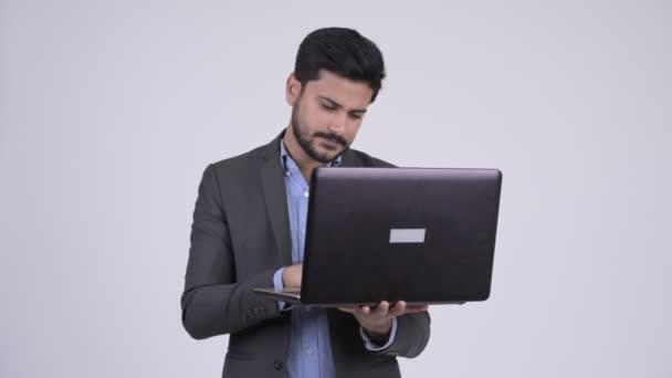 Boldog fiatal szakállas indiai üzletember gondolkodás laptop használata közben