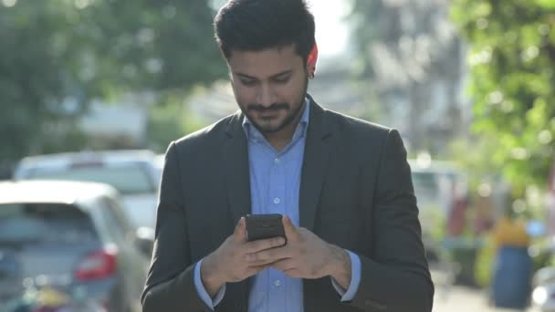 Young happy bearded Indian businessman using phone outdoors