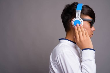 Young Asian teenage boy listening to music against gray backgrou