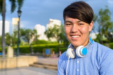 Young Asian teenage boy wearing headphones while relaxing at the