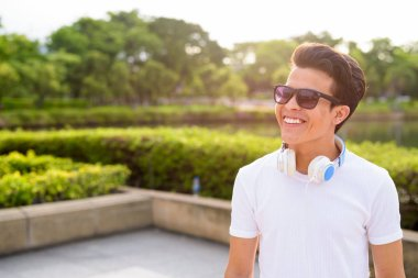 Young Asian man wearing headphones while relaxing at the park