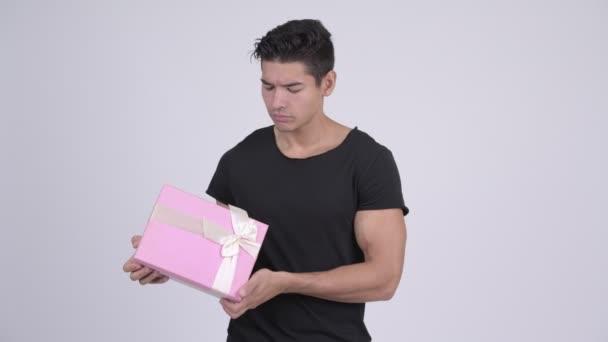 Mladý šťastný multietnické muž myšlení podržíte-dárková krabička