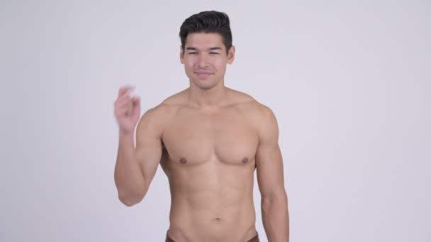 Šťastný mladý pohledný svalnatý shirtless muž směřující nahoru