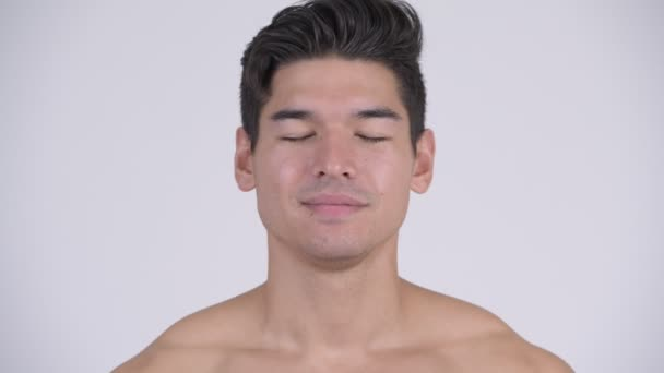 Young handsome muscular shirtless man relaxing with eyes closed