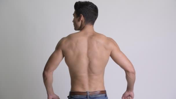 Fiatal izmos félmeztelen férfi mutatja a hát izmait hátulnézet