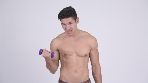 Mladý pohledný svalnatý shirtless muž cvičení s činkami